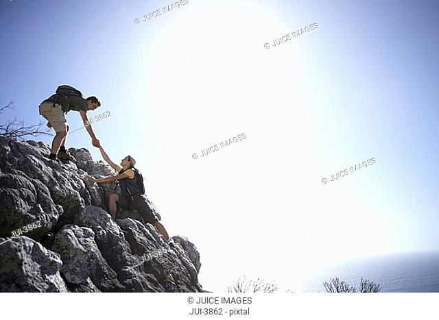 Rock climbing couple ascending rock in bright sunlight, man offering woman helping hand, side view