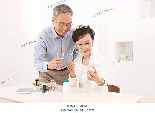Senior couple holding medicine and smiling
