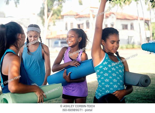 Schoolgirls preparing for yoga practice on school sports field