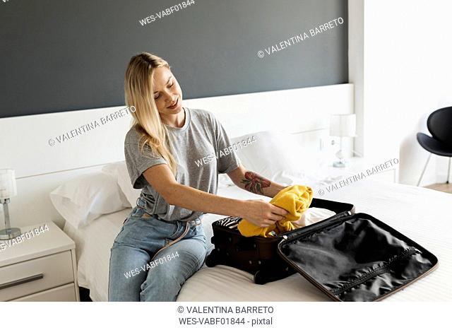 Smiling young woman sitting on bed with suitcase