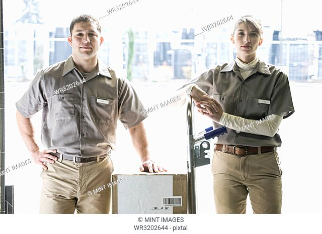 A team portrait of two Caucasian female and Hispanic male uniformed warehouse workers