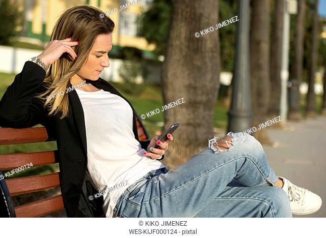 Spain, Puerto Real, woman sitting on a bench looking at smartphone
