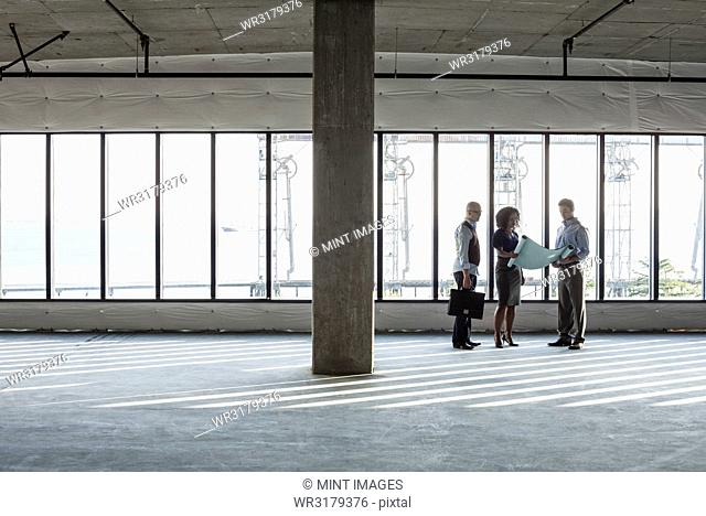 Group of business people looking at a new empty raw office space