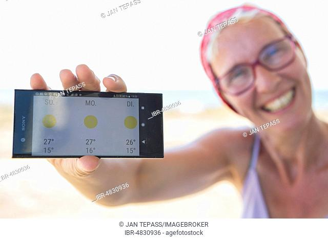 Laughing woman on the beach happy about sunny weather in the weather forecast on her smartphone, Normandie, France