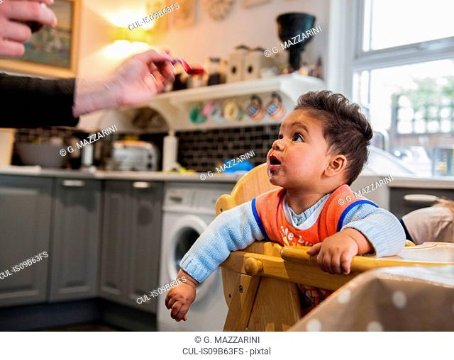 Baby boy in highchair being fed