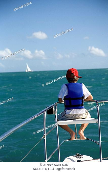Boy in life vest sitting on edge of sailboat