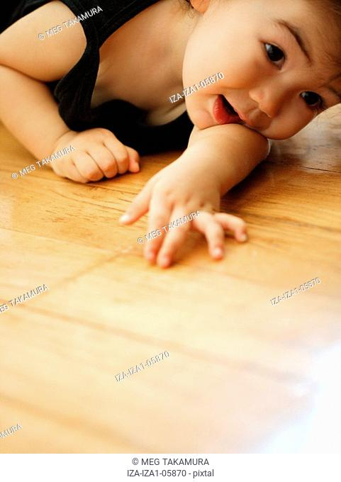 Close-up of a baby girl lying on the floor