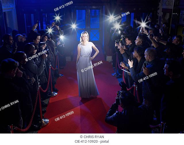 Fans and paparazzi surrounding female celebrity posing on red carpet
