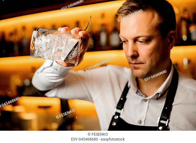 Tow-head barman at the pub mixing alcoholic cocktail with ice using strainer and crystal glass