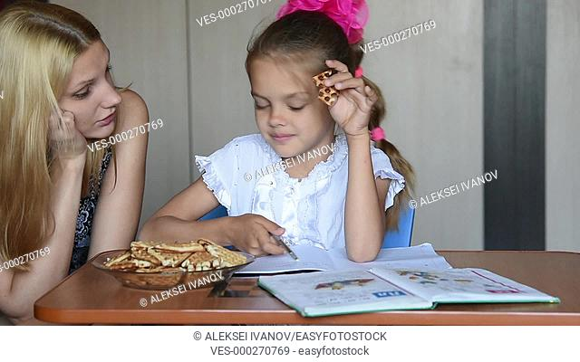 Seven-year school girl eating homemade liver tells mom about homework
