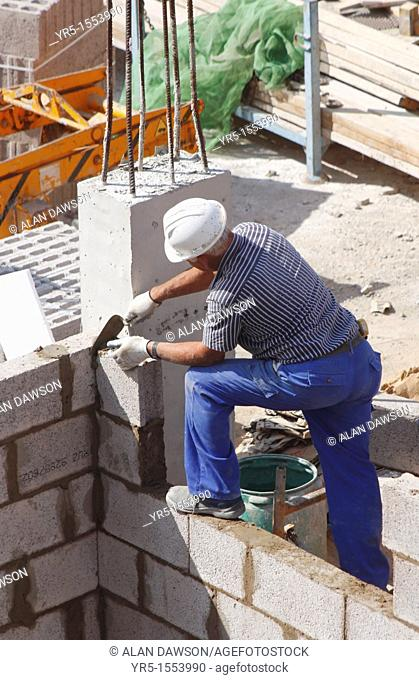 Construction worker building new house on building site on Gran Canaria, Canary Islands, Spain