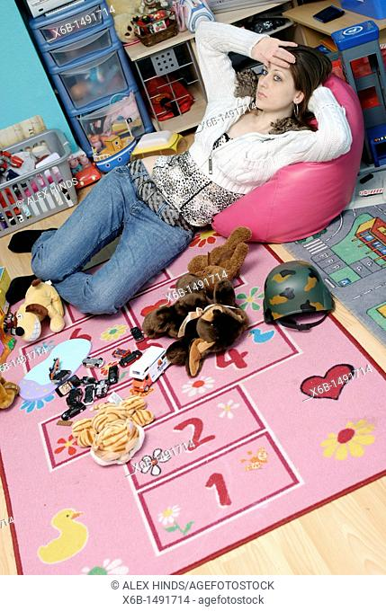 A weary young mum resting for a moment before tidying her children's messy playroom