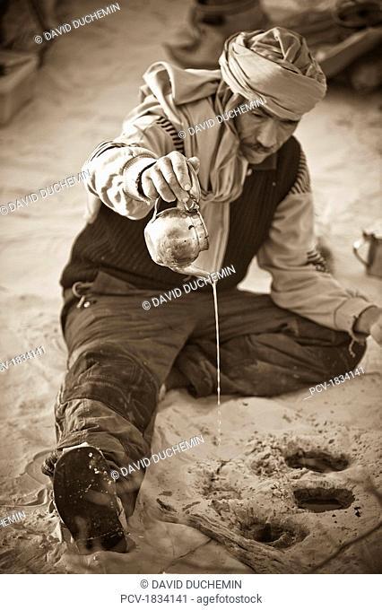 Douz, Sahara Desert, Tunisia, Man pouring oil onto ground