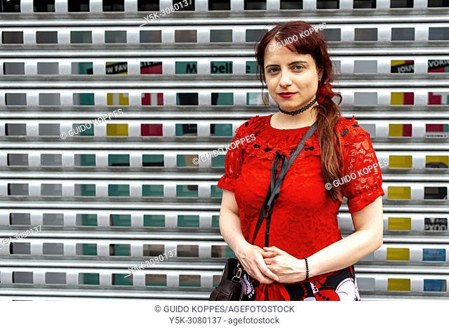 Bijlmer, Amsterdam, Netherlands. Young, red haired woman leaning against a store window shutter and fence. Stores usually use these fences and blinds to protect...