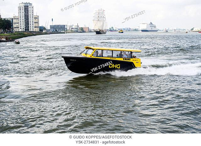 Rotterdam, Netherlands. DHG Watertaxi racing to it's destination over the waters of Nieuwe Maas river, down town