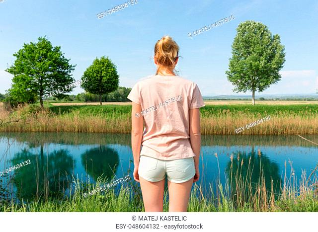 Young woman wearing casual summer clothes enjoying beautiful view of peaceful countryside. Trees on the meadow reflecting in the river