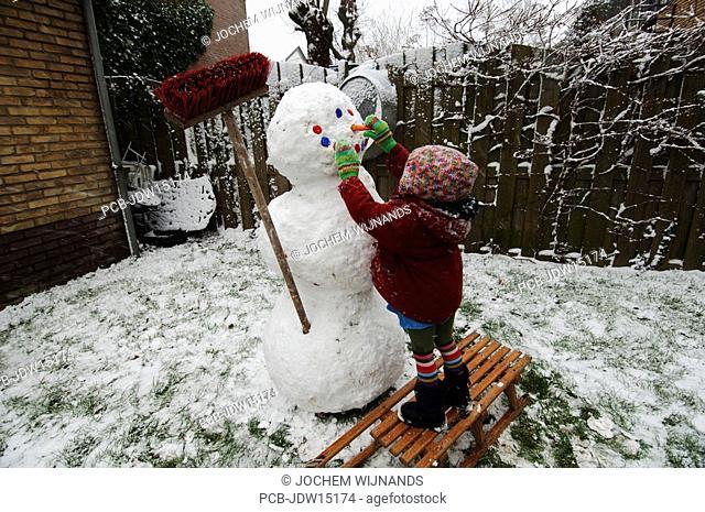 Three year old girl making a snowman in her garden