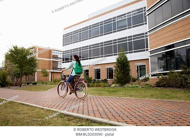 Caucasian student riding bicycle on campus