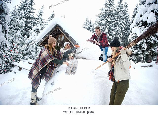 Austria, Altenmarkt-Zauchensee, friends building up big snowman at wooden house