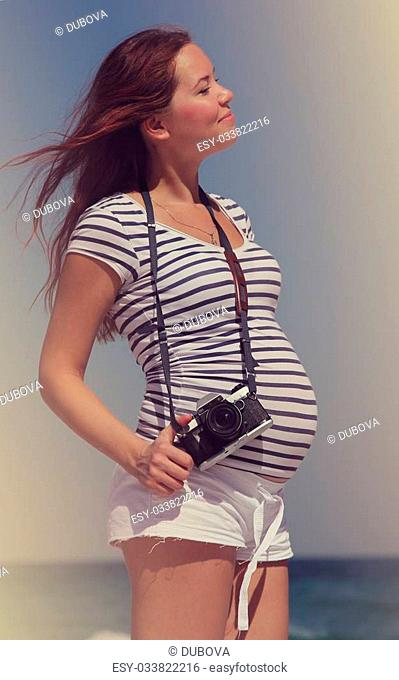 Young pregnant woman holding vintage camera. Photo in old color image style