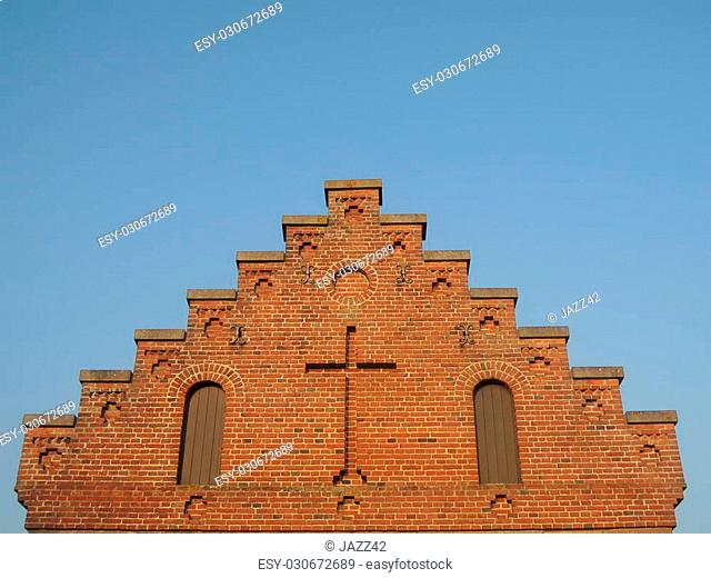 Staircase to heaven - gable of old Danish rural church with cross