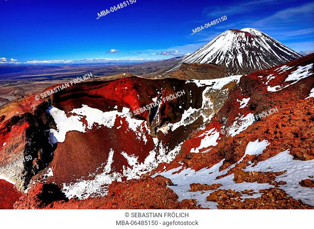The red crater of the Tongariro volcano, with snow and volcano cone of the Mt. Ngauruhoe