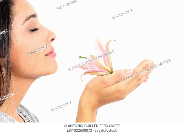 Close up of a beautiful woman profile smelling a pink flower
