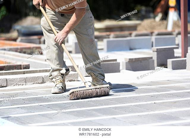 A man using a brush on a cement floor on a construction site