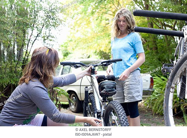 Two women mountain bikers checking cycles in forest