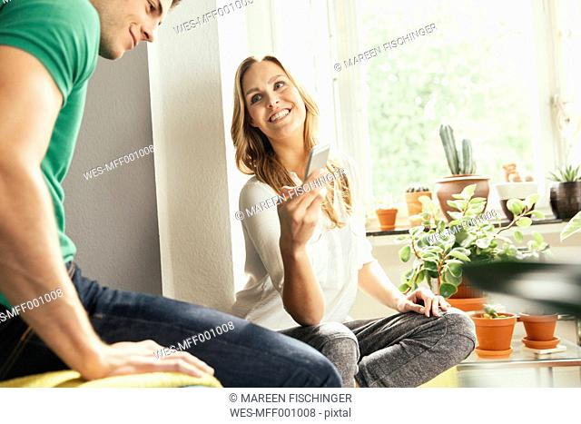 Germany, Bonn, Young woman sitting between plants at home, showing a young man something on her cell phone
