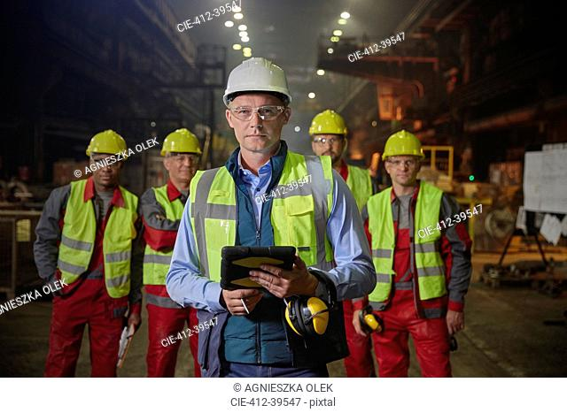 Portrait confident supervisor and steelworkers in steel mill
