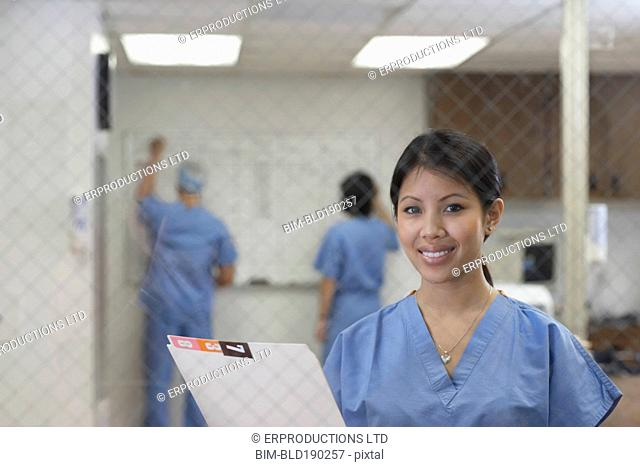 Asian female medical professional holding chart