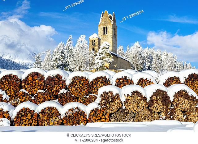 Trunks and old church in Celerina with pristine snow. Engadine, Switzerland, Europe