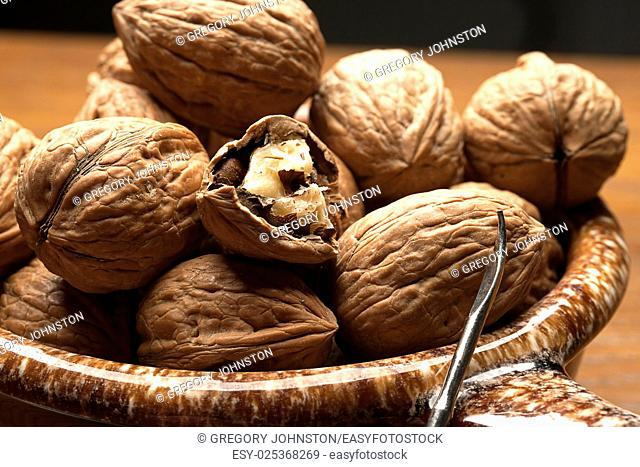 A group of mostly unshelled walnuts and a pick