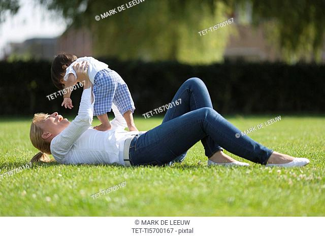 Mother with baby 6-11 months playing on grass