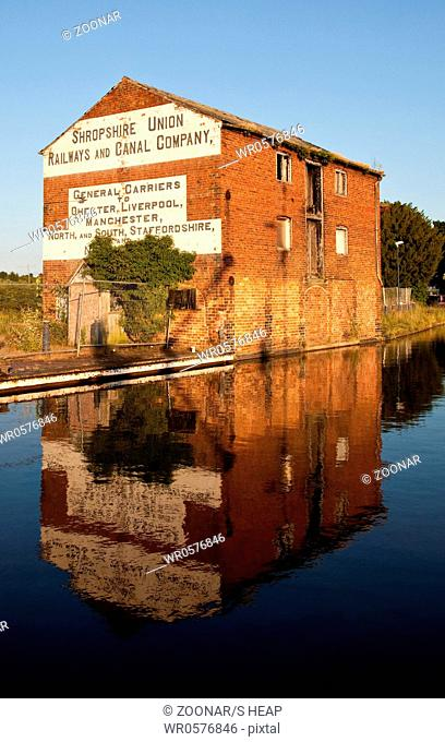 Old warehouse reflected on still evening in the waters of the canal