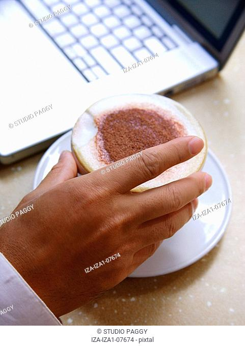 Close-up of a man's hand holding a coffee cup