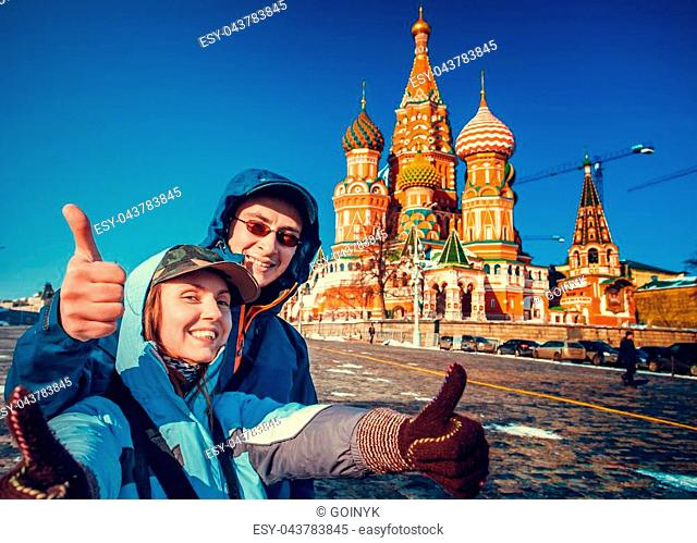 Happy tourists sightseeing city with fingers up next to Saint Basil's Cathedral. Red Square, Moscow, Russia. Holiday, travel, recreation