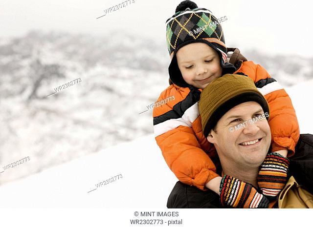 A man carrying a young child on his shoulders