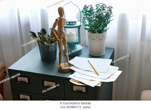 Wooden artist mannequin on filing cabinet, with paper and pencil