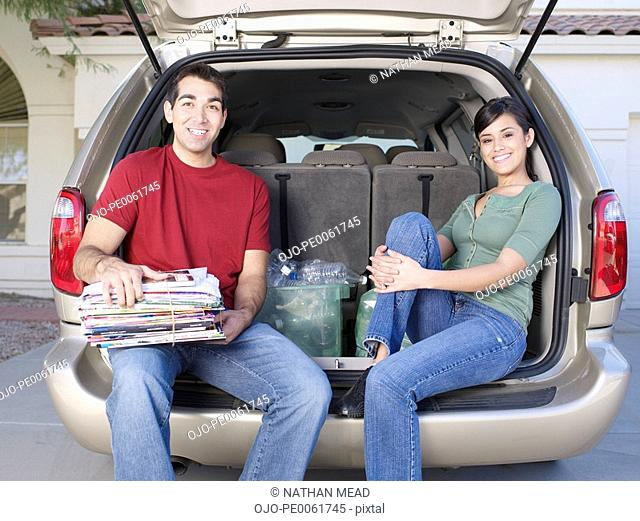 Man and woman sitting in back of van with bin of recyclable materials smiling