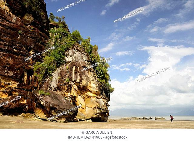 Malaysia, Borneo, Sarawak, Bako National Park, woman walking on Telok Assam beach near a cliff and rocks