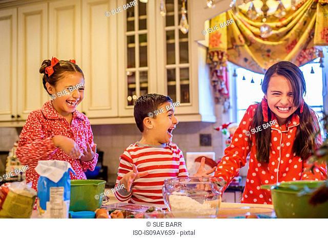 Children wearing pyjamas at kitchen counter baking, laughing