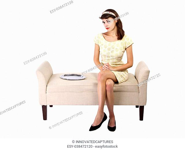 young female looking unsure sitting next to an empty dessert tray. empty serving tray for composites