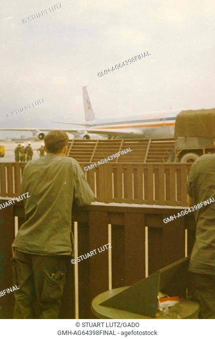 Soldier standing behind a wood fence, looking at an American Airlines plane, and other soldiers, on the tarmac, Danang Airport, Vietnam, 1964