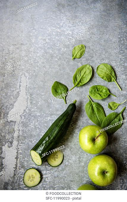 Cucumber, spinach leaves and apples (seen from above)