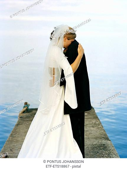 Scandinavia, Sweden, Oland, Groom and bride embracing on jetty