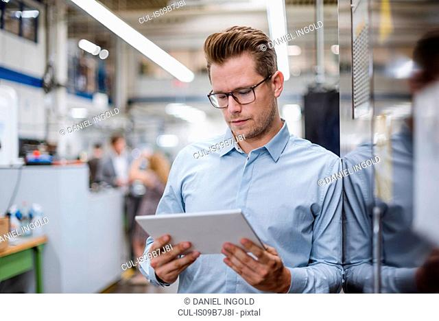 Male manager looking at digital tablet in factory