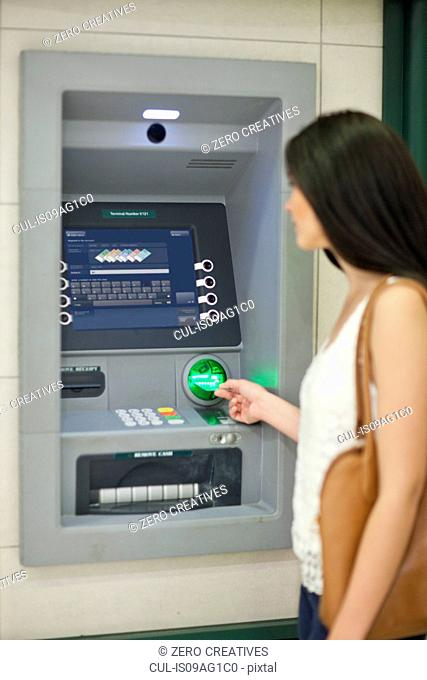 Young woman withdrawing money at cash machine
