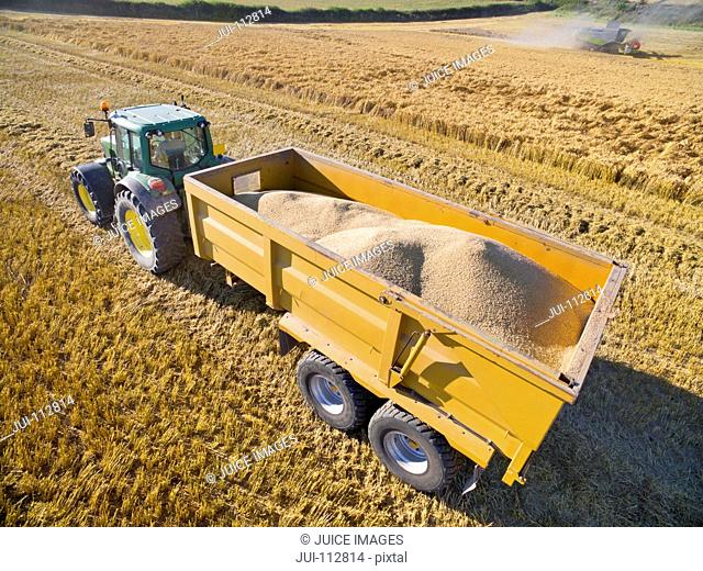 Aerial view of tractor trailer carrying harvested barley in field